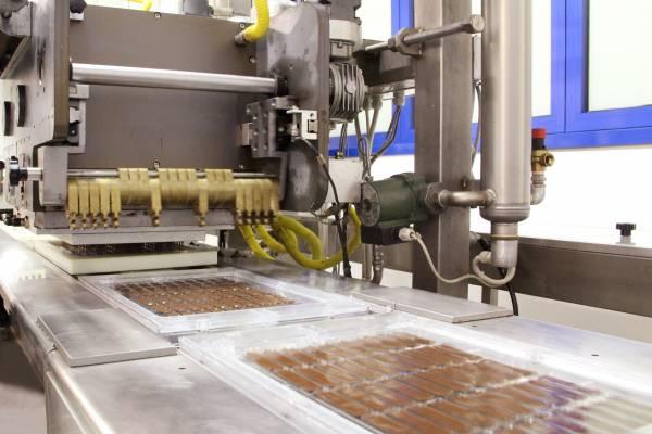 La modellatrice riempie di cioccolato ogni foglio rpeformato