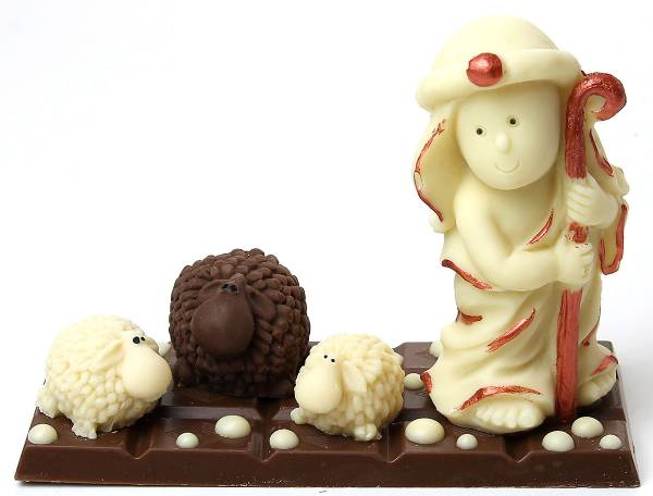 Decorazione di pasticceria realizzata con tre agnelli e un pastore di cioccolato.
