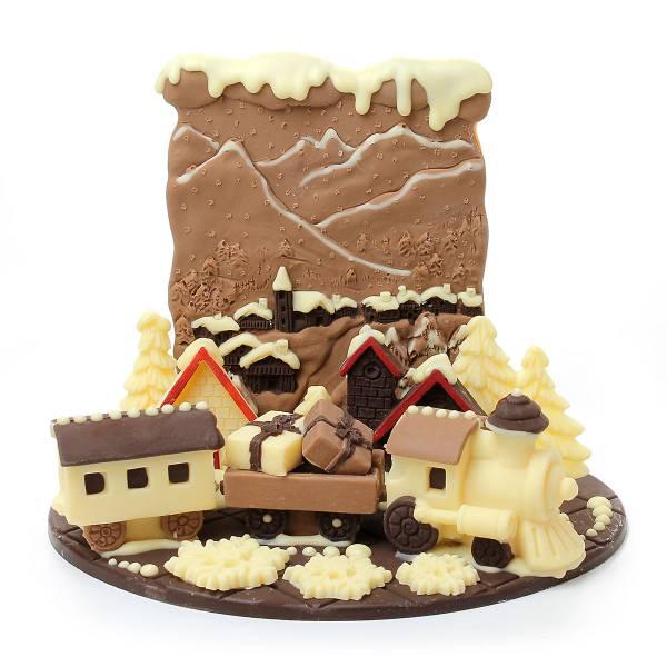 Composizione di cioccolato professionale con trenino e paesaggio di montagna