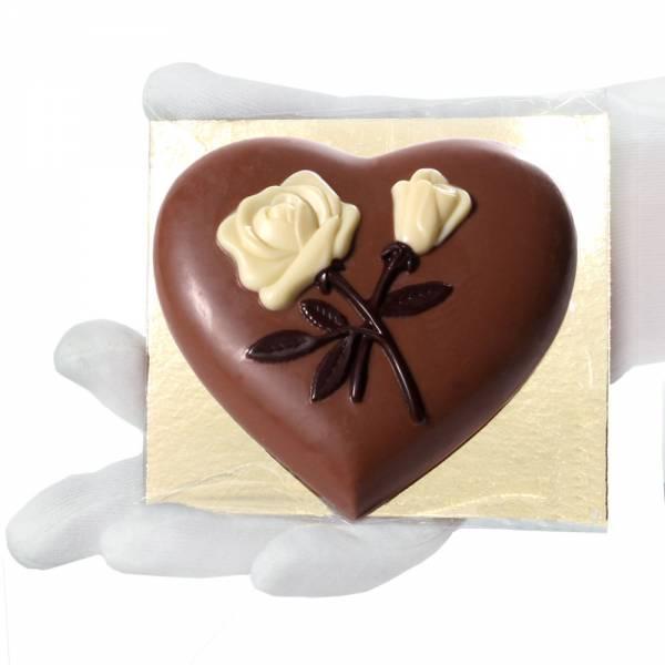 Cuore con rose in rilievo di cioccolato e confezionato in cellophane trasparente con fondo oro.