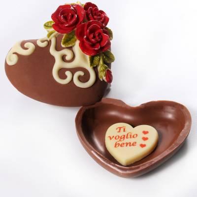 Scatola di cioccolato con coperchio fiorito e dentro un cioccolatino con una scritta d'amore.