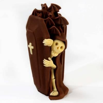 Scheletro di cioccoalto bianco che vuole uscire dalla bara di cioccolato al latte o fondente.
